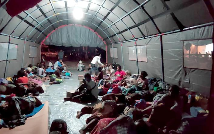 Evacuees sit in a makeshift shelter after Mount Ili Lewotolok erupted spewing a column of smoke and ash 4000 meters high, in Lembata - JOY CHRISTIAN/AFP