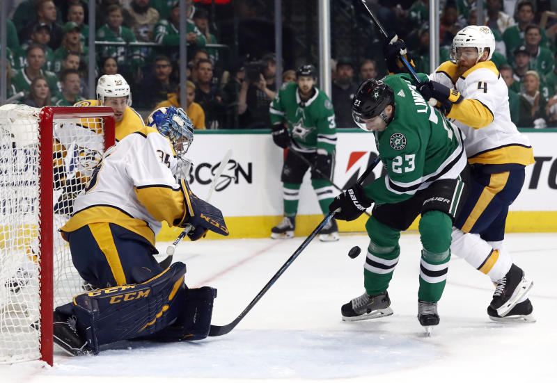 Nashville Predators goaltender Pekka Rinne (35) gets help from defenseman Ryan Ellis (4) while defending the net against pressure from Dallas Stars defenseman Esa Lindell (23) in the first period of Game 3 in an NHL hockey first-round playoff series in Dallas, Monday, April 15, 2019. (AP Photo/Tony Gutierrez)