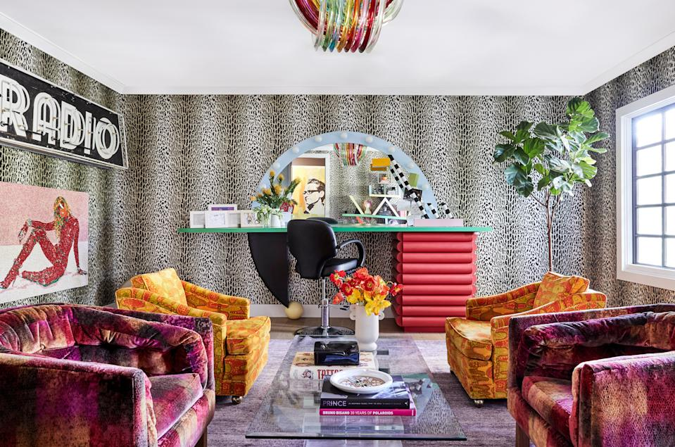 """This is probably one of my favorite rooms because you can't go in here and be unhappy,"" says Tish of Miley's glam-room lounge. ""Everyone ends up going there and just hanging out. Usually, that room is the kitchen, but in this house, it's here."" A vintage Curvati Murano glass rainbow light is centered over vintage armchairs that Miley has had for ""a really long time"" and a lucite coffee table. The whimsical glam station itself was designed by Sanders, with a nod to the technicolor Ettore Sottsass bookcase at the other end of the space."