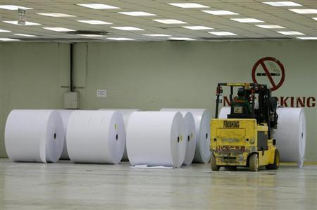 Rolls of finished paper are stored in the finishing area in pulp and paper factory in Kerinci