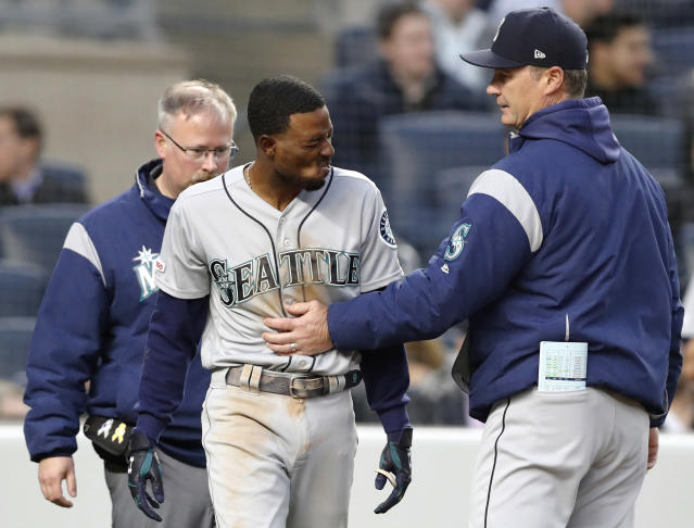 Seattle Mariners manager Scott Servais, right, and a Mariners trainer check on Dee Gordon, center, who was hit by a pitch during the third inning of the team's baseball game against the New York Yankees, Thursday, May 9, 2019, in New York. Gordon was removed from the game. (AP Photo/Kathy Willens)