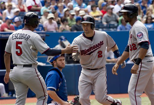 Toronto Blue Jays catcher Josh Thole watches as Minnesota Twins' Brian Dozier (2) is congratulated by teammates Eduardo Escobar (5) and Aaron Hicks (32) after scoring them on his three-run home run during the seventh inning of a baseball game in Toronto on Saturday, July 6, 2013. (AP Photo/The Canadian Press, Frank Gunn)