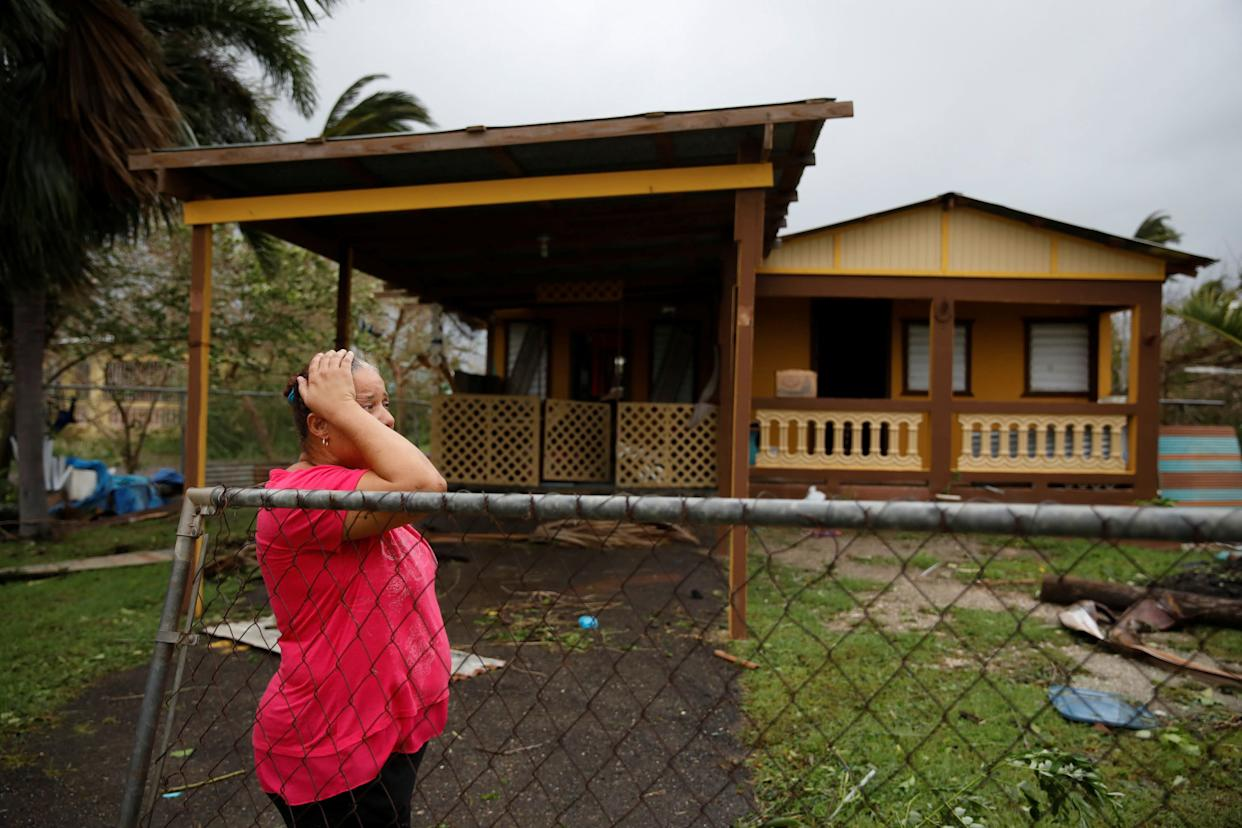 A woman reacts while looking at the damage to her house after the area was hit by Hurricane Maria in Guayama, Puerto Rico.