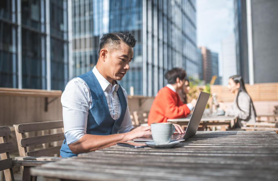 Side view of mature businessman drinking coffee while using technologies. Confident professional is sitting at table. He is working at outdoor cafe.