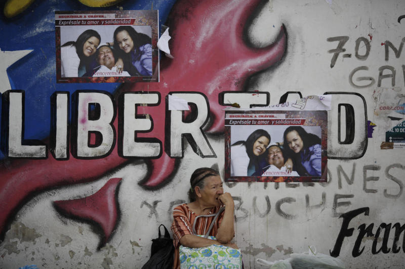 A woman sits against a wall covered with pictures of Venezuela's President Hugo Chavez with his daughters Maria Gabriela, left, and Rosa Virginia in Caracas, Venezuela, Tuesday, Feb. 26, 2013. The government said last week that the country's ailing president was continuing unspecified medical treatments at the military hospital in Caracas. Chavez's sudden return to Venezuela after more than two months of cancer treatments in Cuba has fanned speculation that the president could be preparing to relinquish power and make way for a successor and a new election. (AP Photo/Ariana Cubillos)