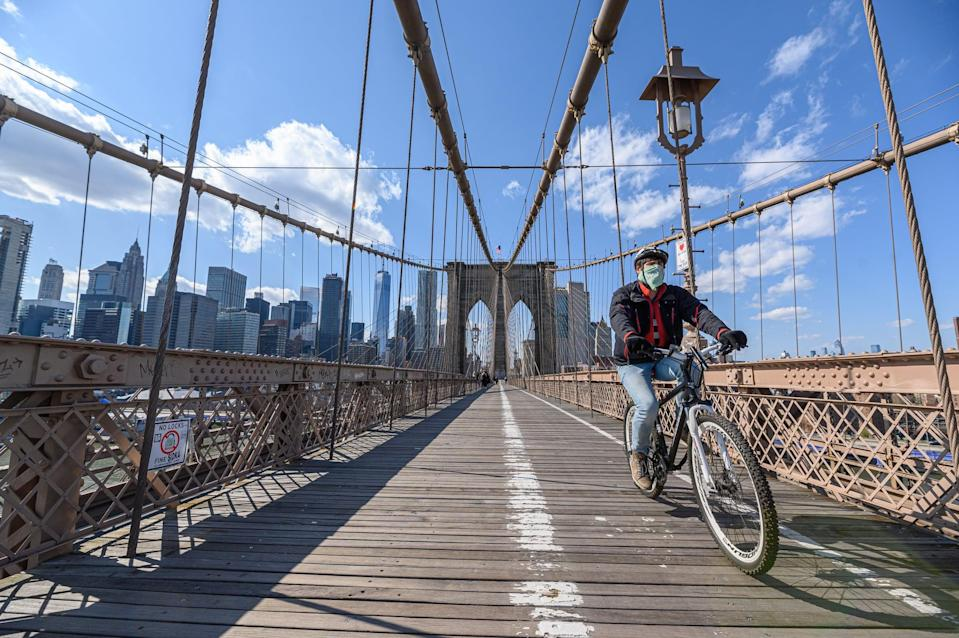 NEW YORK, NY - APRIL 15: A man wearing a protective mask rides a bicycle on the Brooklyn Bridge during the coronavirus pandemic on April 15, 2020 in New York City. COVID-19 has spread to most countries around the world, claiming over 134,000 lives lost with over 2 million infections reported. (Photo by Noam Galai/Getty Images)