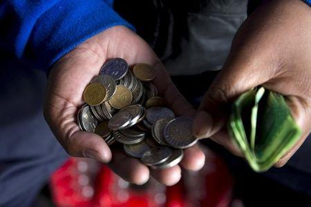 A street trader counts out change for a customer in Durban