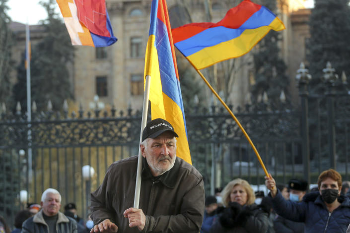 Opposition demonstrators, some of them with Armenian national flags rally to pressure Armenian Prime Minister Nikol Pashinyan to resign in Yerevan, Armenia, Wednesday, March 3, 2021. Thousands of opposition supporters are rallying in the Armenian capital to demand the resignation of the country's prime minister amid a heavy presence of security forces. Prime Minister Nikol Pashinyan has faced the opposition demands to step down since he signed a peace deal that ended six weeks of fighting over the Nagorno-Karabakh region, in which Azerbaijan routed the Armenian forces. (Hrant Khachatryan/PAN Photo via AP)
