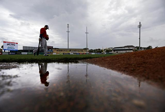 Washington Nationals' Brandon Laird walks past a puddle on the field as it rains before the start of an exhibition spring training baseball game against the Miami Marlins, Monday, March 24, 2014, in Jupiter, Fla. (AP Photo/David Goldman)