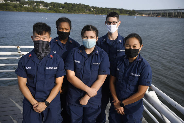 In this Monday Sept. 14, 2020 photo, From the left, Coast Guard Academy Cadets Tyler Huynh, Branyelle Carillo, Mia Haskovec, Henry Smith, and Jordan Park, pose for a photograph at the Seamanship Sailing Center at the United State Coast Guard Academy in New London, Conn. A group of Coast Guard cadets spent part of their summer filling in on a critical national security mission after a case of COVID-19 sidelined crew members on a cutter being sent to patrol the US-Russia border. (AP Photo/Jessica Hill)