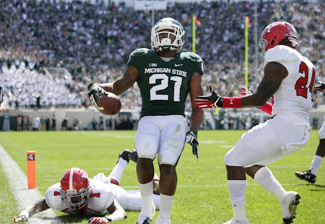 Michigan State receiver Andre Sims Jr. (21) scores on a 13-yard pass reception between Youngstown State's Julius Childs (1) and Jamarious Boatwright, right, during the first quarter of an NCAA college football game, Saturday, Sept. 14, 2013, in East Lansing, Mich. (AP Photo/Al Goldis)