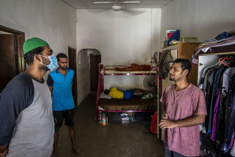 Shohel Mollah (left) talking to computer science graduate Ahmmad Ali who now works as a cleaner. — Picture by Shafwan Zaidon
