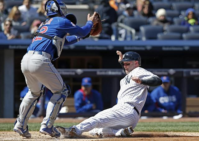 Chicago Cubs catcher John Baker catches the late throw as New York Yankees' Brian McCann scores on Dean Anna's fourth-inning sacrifice fly in Game 1 of an interleague baseball doubleheader at Yankee Stadium in New York, Wednesday, April 16, 2014. (AP Photo/Kathy Willens)