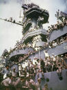 FILE - Servicemen, reporters, and photographers perch on the USS Missouri on Sept. 2, 1945, for the onboard ceremony in which Japan surrendered in Tokyo Bay, ending World War II. Several dozen aging U.S. veterans, including some who were in Tokyo Bay as swarms of warplanes buzzed overhead and nations converged to end World War II, will gather on the battleship in Pearl Harbor in September to mark the 75th anniversary of Japan's surrender, even if it means the vulnerable group may be risking their lives again amid the coronavirus pandemic. (AP Photo, File)
