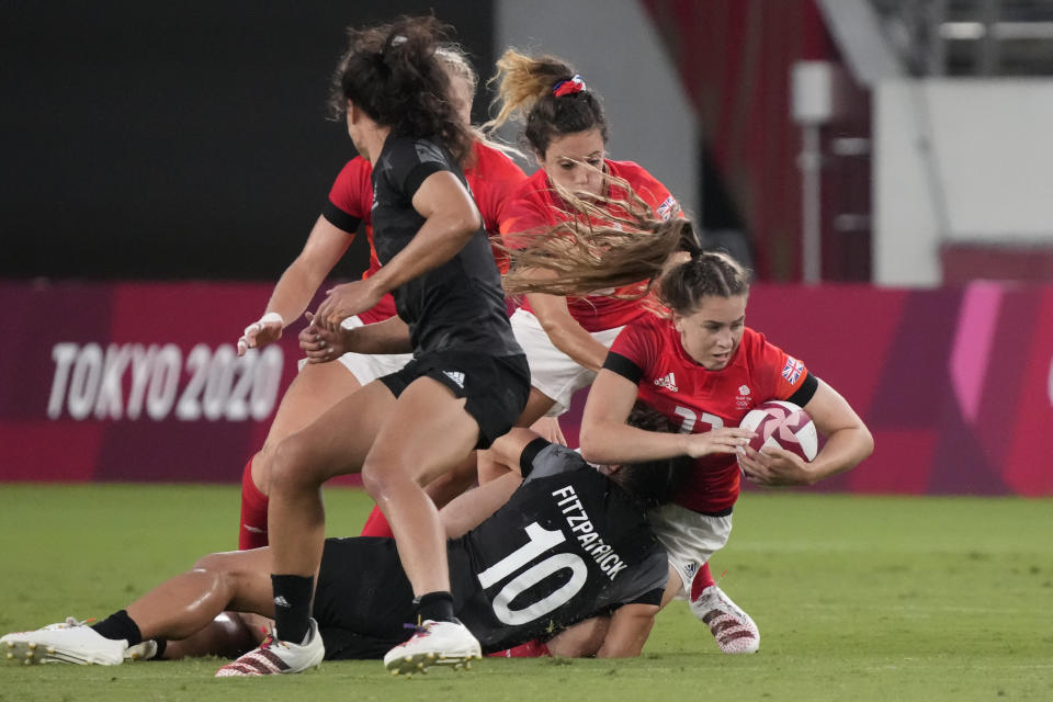 Britain's Holly Aitchison, right, is tackled by New Zealand's Theresa Fitzpatrick, bottom, in their women's rugby sevens match at the 2020 Summer Olympics, Thursday, July 29, 2021 in Tokyo, Japan. (AP Photo/Shuji Kajiyama)