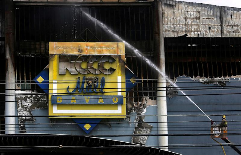 On Sunday, a day after the blaze began, firefighters were still unable to enter the still-smouldering building. (Marconi Navales / Reuters)