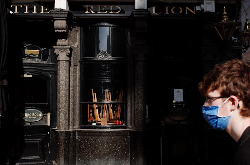 A man wearing a face mask walks past upturned stools in the window of The Red Lion pub, closed due to coronavirus, on a near-deserted Whitehall in London, England, on May 28, 2020. The UK is now in its tenth week of coronavirus lockdown, with total deaths now standing at 37,837, according to today's updated count from the Department of Health and Social Care. British Prime Minister Boris Johnson meanwhile remains under unrelenting pressure over his refusal to sack his top aide, Dominic Cummings, who stands accused of flouting strict stay-at-home instructions by driving with his wife and son from London to County Durham on March 27 to stay at a family property. The reporting of the journey, and that of a subsequent trip to the Durham market town of Barnard Castle, has provoked huge public outcry since the story broke last Friday. (Photo by David Cliff/NurPhoto via Getty Images)