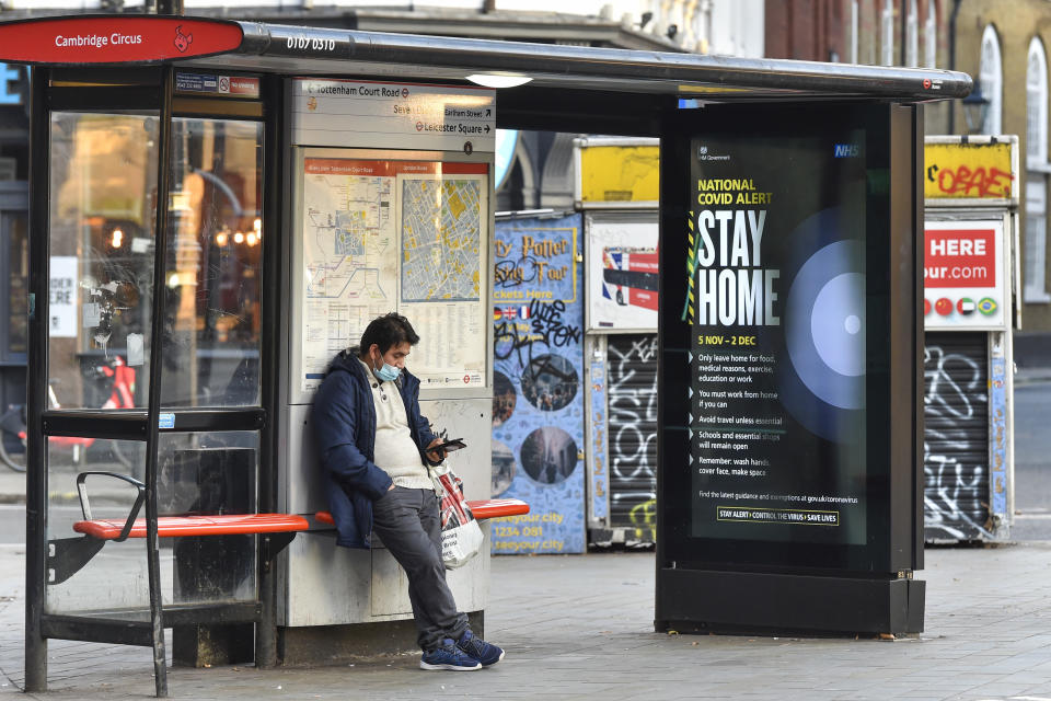 "A man using his phone at a Bus Stop in Cambridge Circus, where a Government Covid 19 level alert saying ''Stay Home"" displays on an electronic screen. England has entered into the 2nd Lockdown due to the Pandemic. (Photo by Dave Rushen / SOPA Images/Sipa USA)"