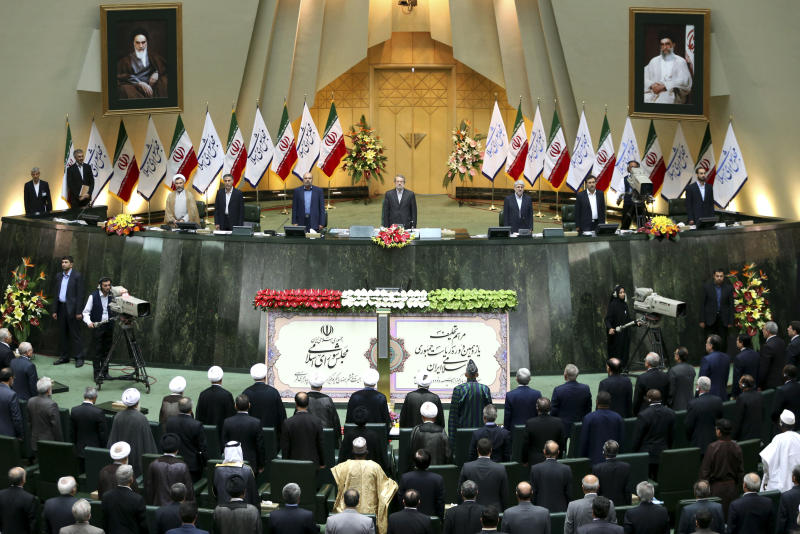 "Iran's parliament presiding board members, top row, Iranian and foreign leaders and top officials, all back to camera, listen to Iran's national anthem at the start of the ceremony for the new President Hasan Rouhani's swearing-in at the parliament in Tehran, Iran, Sunday, Aug. 4, 2013. Rouhani replaced Mahmoud Ahmadinejad, who was in power since 2005. Rouhani on Sunday called on the West to abandon the ""language of sanctions"" in dealing with his country over its contentious nuclear program, hoping to ease the economic pressures now grinding its people. (AP Photo/Ebrahim Noroozi)"