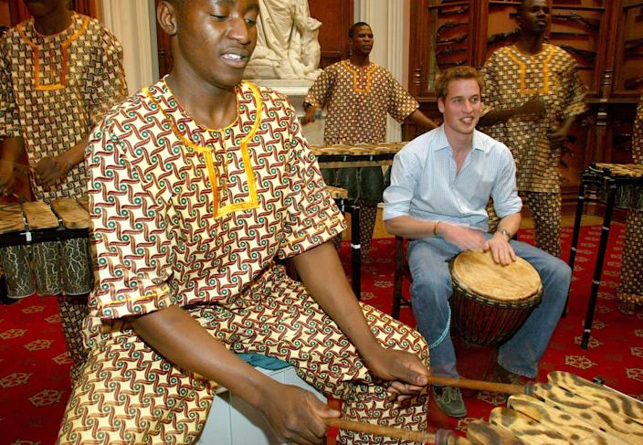 """Prince William plays the drums as the Shakarimba band, who have been flown in from Botswana to perform at the Prince's 21st birthday party on June 21, rehearse in the Queen's Guard Chamber at Windsor Castle. The Prince has chosen an """"Out of Africa"""" theme for his party and the more than 300 family and friends who have been invited have been asked to wear fancy dress. (Photo by Anwar Hussein/WireImage)"""