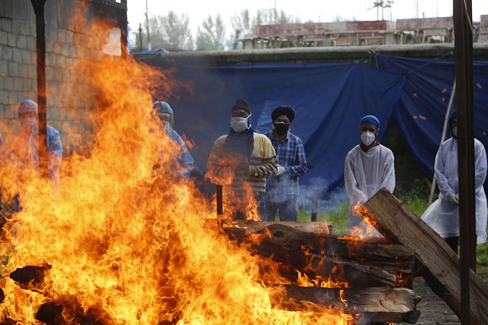 SRINAGAR, INDIA - MAY 25: Relatives and volunteers look on while a Covid-19 victim is cremated at a cremation ground on May 25, 2021 in Sringar, India. (Photo by Waseem Andrabi/Hindustan Times via Getty Images)