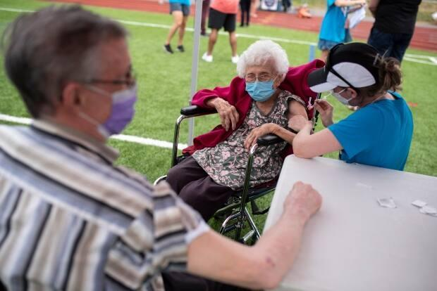 Dr. Katie Baldwin delivers a COVID-19 vaccine to Jeanne St. Onge, 101, as her husband Denis, 92, waits for his dose, at an outdoor, pop-up vaccination clinic nicknamed 'Jabapalooza' held in Ottawa this weekend. On Sunday, city health officials reported 36 new cases  and another two deaths. (Justin Tang/The Canadian Press - image credit)