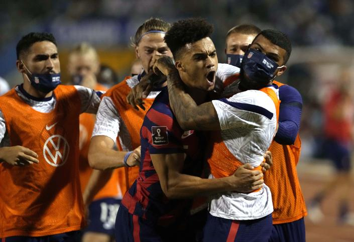 United States's Antonee Robinson, center, celebrates with his teammates after scoring his side's opening goal against Honduras during a qualifying soccer match for the FIFA World Cup Qatar 2022, in San Pedro Sula, Honduras, Wednesday, Sept. 8, 2021. (AP Photo/Moises Castillo)