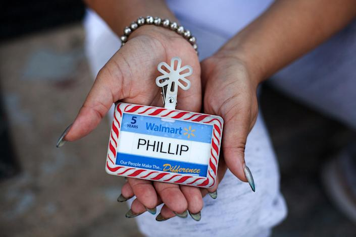 Image: Angela McMiller holds her late brother Phillip Thomas' Walmart employee badge. (Eddie Quinones / for NBC News)