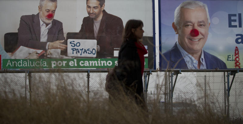 A woman walks past posters with portraits of candidates for the upcoming Andalusian elections, from the conservative Popular Party candidate Javier Arenas, right, and from the Socialist party Jose Antonio Grinyan, left, in the outskirts of Seville, Spain, Sunday March 25, 2012. Spaniards are voting in regional elections that could see the conservative Popular party oust Socialist opponents from office in the latter's traditional power base of Andalucia. More than 7 million voters are called to go to the polls Sunday in that southern region and also in northern Asturias. The posters have been defaced to make the candidates look like clowns. (AP Photo/Miguel Angel Morenatti)