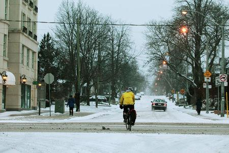 Cyclist navigates traffic after an overnight snow storm, in Toronto