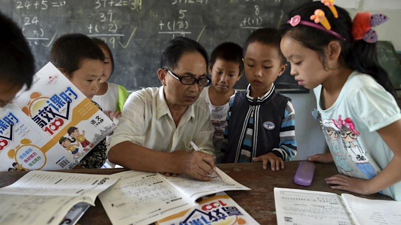 """A teacher (C) speaks to students inside a classroom of Dalu primary school in Gucheng township of Hefei, Anhui province, China, September 8, 2015. The school, opened in 2006 and has never acquired a legal license, may face a shutdown order from the government. There are currently over 160 students in the school, mostly """"leftover children"""", whose parents left their hometown to earn a living, local media reported."""