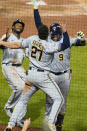 Milwaukee Brewers' Manny Pina (9) celebrates with Lorenzo Cain, left, and Willy Adames (27) after hitting a two-run home run off Pittsburgh Pirates relief pitcher Austin Davis during the eighth inning of a baseball game in Pittsburgh, Thursday, July 29, 2021. (AP Photo/Gene J. Puskar)