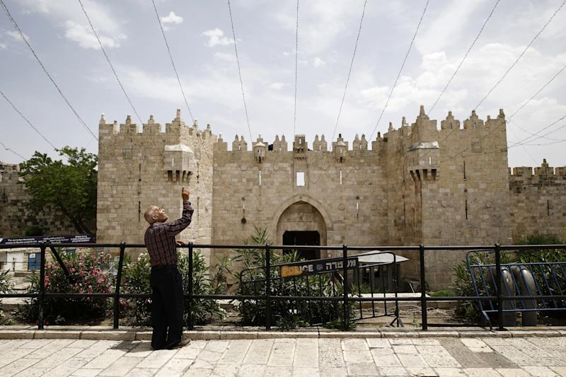 A man points as he looks up while standing near Damascus Gate in Jerusalem's Old City. (Photo: Nir Elias/Reuters)