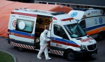 FILE PHOTO: A paramedic walks near an ambulance amid the coronavirus disease (COVID-19) outbreak, in front of a hospital in Warsaw