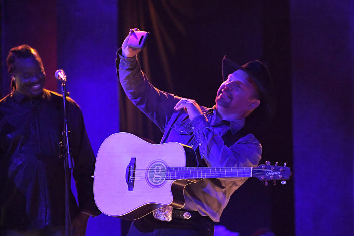 """FILE - In this Wednesday, Nov. 13, 2019, file photo, Garth Brooks performs """"Dive Bar"""" at the 53rd annual CMA Awards at Bridgestone Arena in Nashville, Tenn. Add Garth Brooks to the lineup of entertainers at the inauguration of President-elect Joe Biden. Brooks, who joins Lady Gaga and Jennifer Lopez among others, performed during the inaugural celebration of President Barack Obama in 2009. He turned down a chance to play for President Donald Trump in 2017, citing a scheduling conflict. (AP Photo/Mark J. Terrill, File)"""