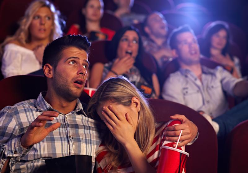 Moviegoers reacting to a horror film.