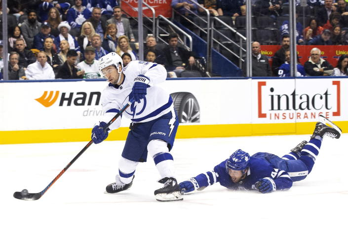 Tampa Bay Lightning center Tyler Johnson (9) gets a shot away as Toronto Maple Leafs defenseman Morgan Rielly (44) defends during the second period of an NHL hockey game Tuesday, March 10, 2020, in Toronto. (Chris Young/The Canadian Press via AP)