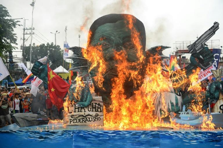 Activists burn an effigy of Philippine President Rodrigo Duterte depicted as a sea monster, during a protest near congress to coincide with Duterte's state of the nation address in Manila (AFP Photo/TED ALJIBE)