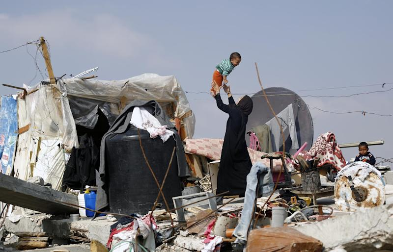 A Palestinian woman plays with her child on the rubble of their family's home which was destroyed during the 50-day Gaza war between Israel and Hamas-led militants in the Gaza Strip, on November 12, 2014