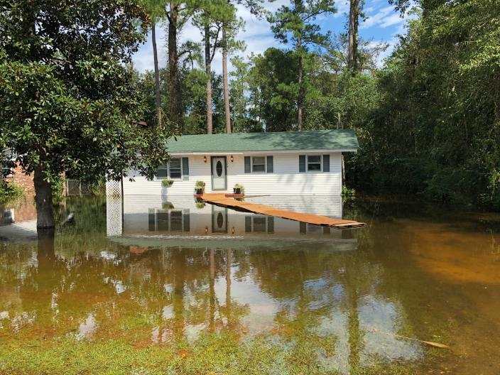 Floodwaters approach a house in Conway, S.C., on Monday, Sept. 17, 2018. Neighbors worry a decision by the state of South Carolina to build a higher wall on the main highway to Myrtle Beach to keep it open might push more floodwaters from the Waccamaw River into neighborhoods. The state says the effect will be negligible. (AP Photo/Jeffrey Collins)