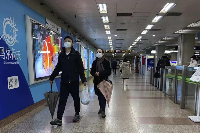 Masked residents walk through a deserted subway station in Shanghai, China, on Sunday, Jan. 26, 2020, as the new viral illness accelerated its spread in China.  The U.S. and Japanese officials announced Sunday they will evacuate personnel and some private citizens aboard a charter flight from the epicenter of the outbreak in the central city of Wuhan. (AP Photo/Erika Kinetz)