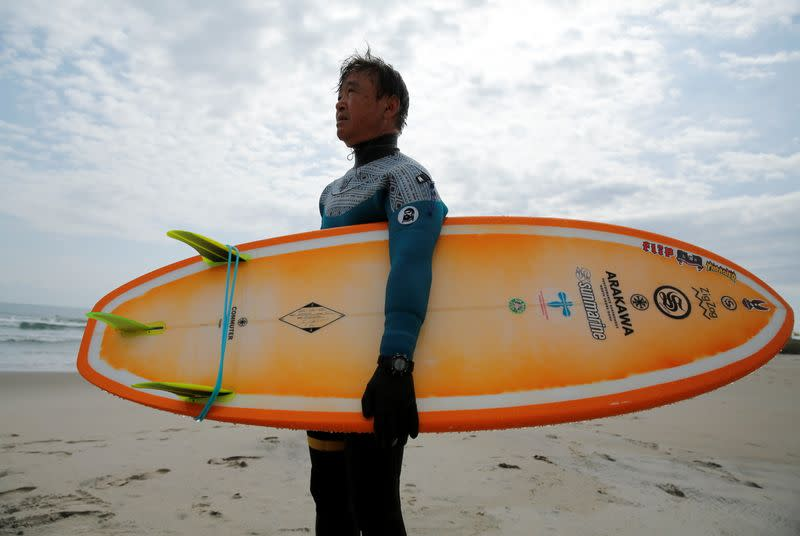 Koji Suzuki, a surfer and a surf shop owner, by the sea in Minamisoma