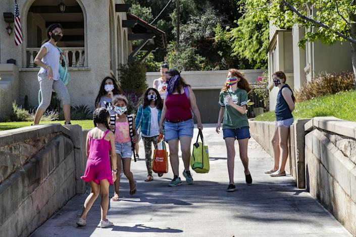 "Students and parents of ""Brothbush Academy"" walk from the Bristows' house to the Furbushes' for a cooking class during home school in the midst of the COVID-19 pandemic. <span class=""copyright"">(Gina Ferazzi / Los Angeles Times)</span>"