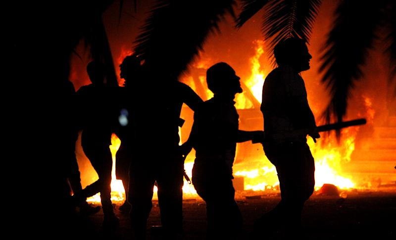 Libyan civilians watch fires in Ansar al-Shariah Brigades compound, after hundreds of Libyans, Libyan Military, and Police raided the Brigades base, in Benghazi, Libya, Friday, Sept. 21, 2012. The recent attack that killed the U.S. ambassador and three other Americans has sparked a backlash among frustrated Libyans against the heavily armed gunmen, including Islamic extremists, who run rampant in their cities. More than 10,000 people poured into a main boulevard of Benghazi, demanding that militias disband as the public tries to do what Libya's weak central government has been unable to. (AP photo/Mohammad Hannon)
