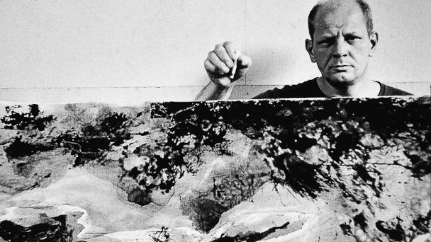 PHOTO: American abstract expressionist painter Jackson Pollock holds a cigarette with one of his paintings in his studio at 'The Springs,' East Hampton, N.Y., Aug. 23, 1953. (Tony Vaccaro/Getty Images))