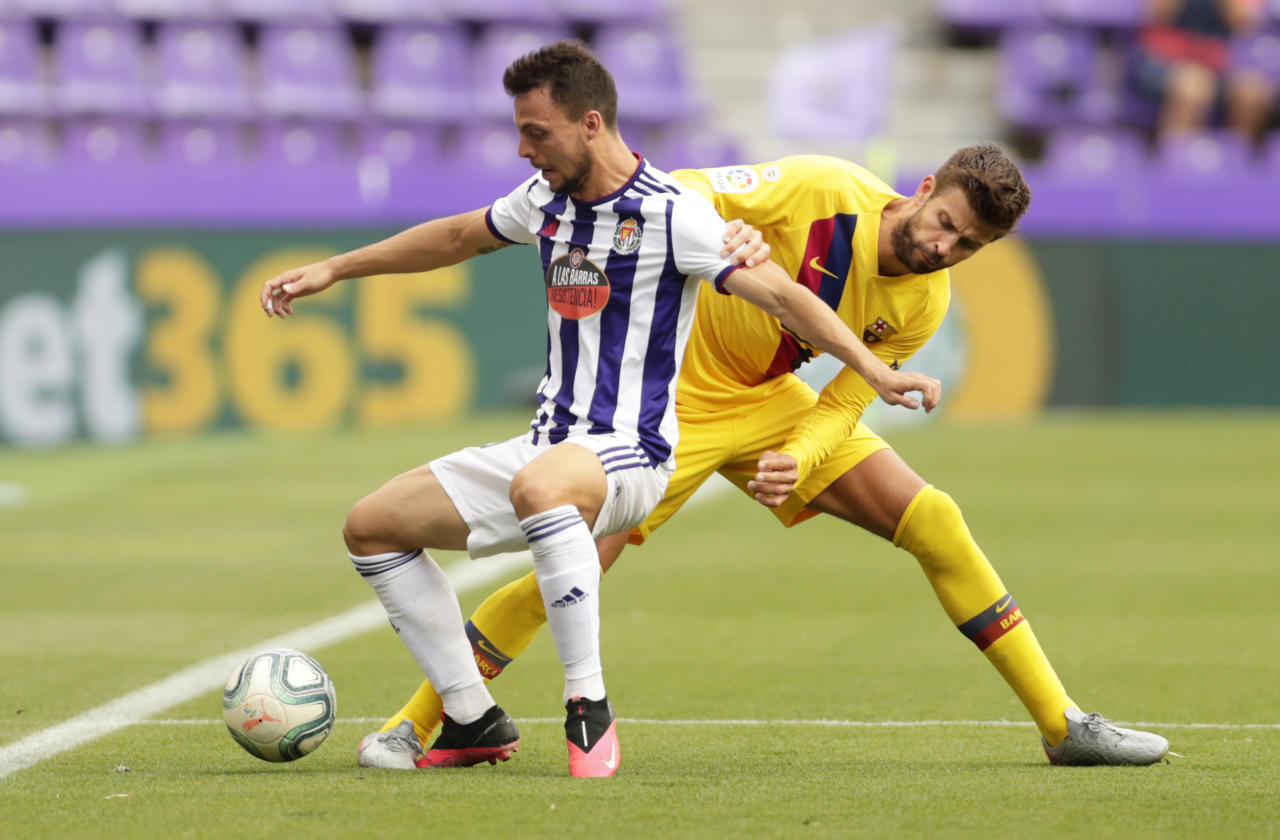 Valladolid's Oscar Plano, left, and Barcelona's Gerard Pique challenge for the ball during the Spanish La Liga soccer match between Valladolid and FC Barcelona at the Jose Zorrilla stadium in Valladolid, Spain, Saturday, July 11, 2020. (AP Photo/Manu Fernandez)