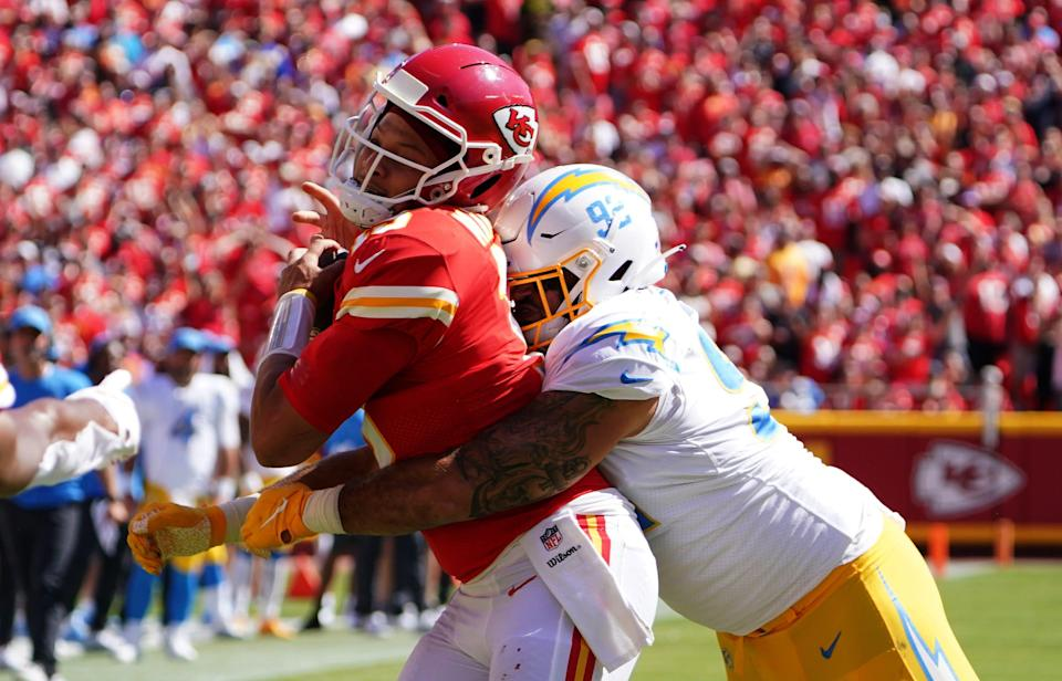 Kansas City Chiefs quarterback Patrick Mahomes (15) is tackled by Los Angeles Chargers defensive tackle Justin Jones (93) during the second half at GEHA Field at Arrowhead Stadium.