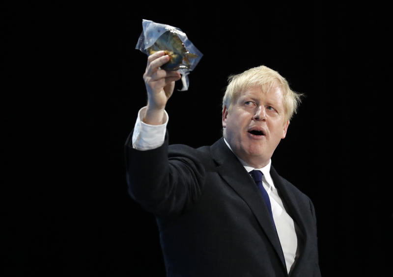 CORRECTS ITEM BEING HELD UP Conservative party leadership candidate Boris Johnson holds up a bagged smoked fish during his speech during a Conservative leadership hustings at ExCel Centre in London, Wednesday, July 17, 2019. The two contenders, Jeremy Hunt and Boris Johnson are competing for votes from party members, with the winner replacing Prime Minister Theresa May as party leader and Prime Minister of Britain's ruling Conservative Party. (AP Photo/Frank Augstein)