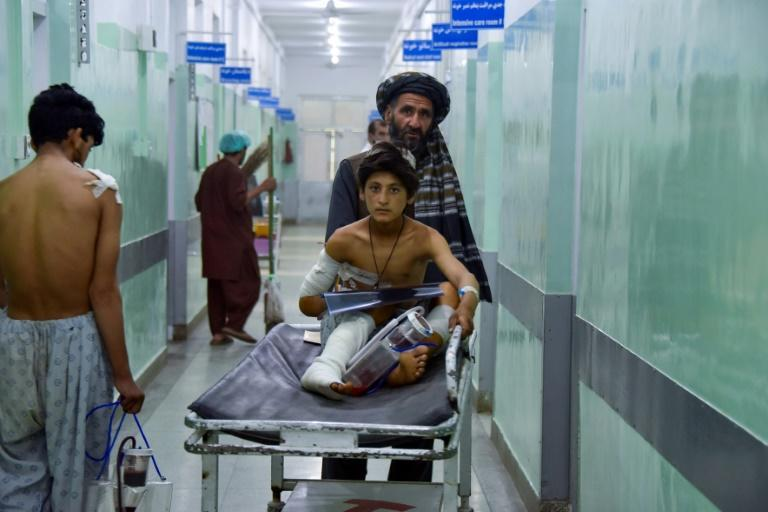 A man pushes an injured boy on a stretcher along a hospital corridor in Kandahar, Afghanistan on May 10, 2021, after a roadside bomb struck a bus overnight, killing at least 11 people