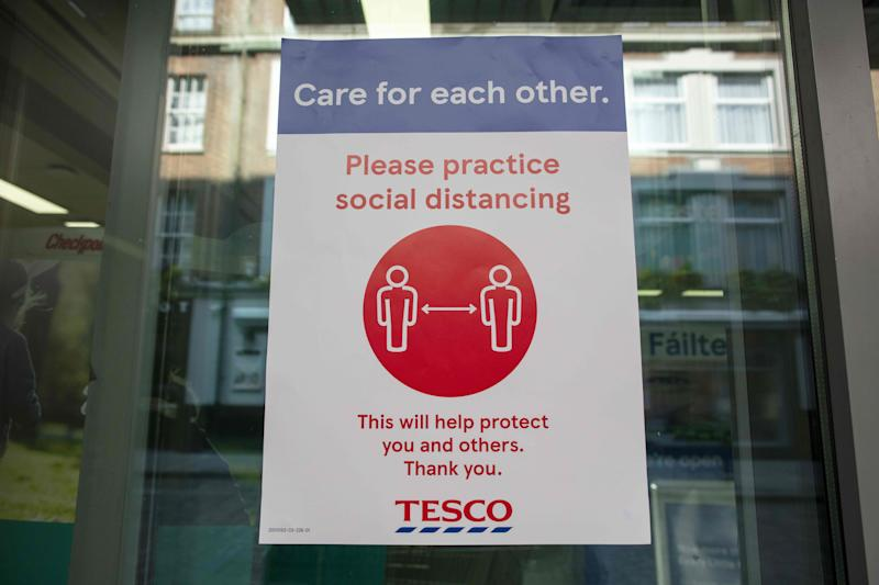 "A sign outside a branch of a Tesco supermarket alerts customers for the need to obey social distancing measures, in Dublin, on March 25, 2020, after Ireland introduced measures to help slow the spread of the novel coronavirus. - Ireland's prime minister Leo Varadkar on Tuesday announced that all non-essential businesses will shut from midnight as part of the country's latest measures to tackle the coronavirus outbreak. ""These are unprecedented actions to respond to an unprecedented emergency,"" he said, adding the measures would remain in place until at least April 19. (Photo by PAUL FAITH / AFP) (Photo by PAUL FAITH/AFP via Getty Images)"